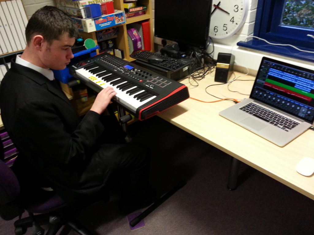 One of the group members using the keyboard, to compose and record his track, on to the laptop.