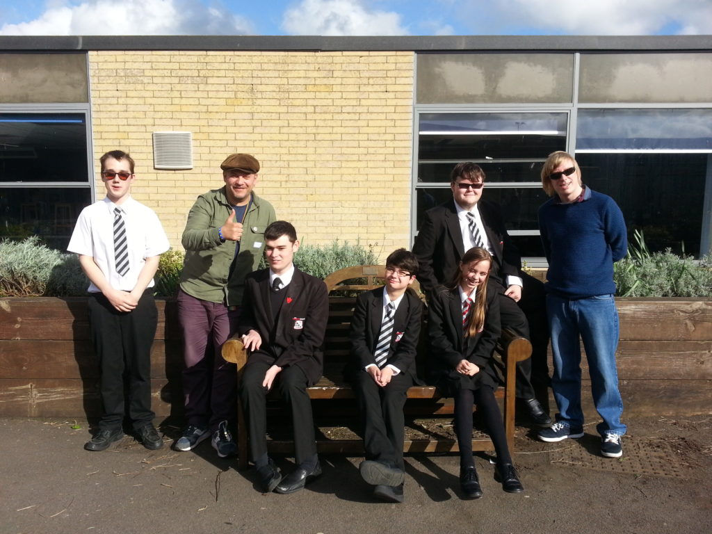 Members of the group with Jim and David, having a group photo in the playground, for the CD cover.
