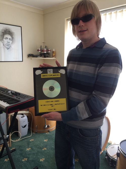 David holding a framed CD, given to the team, by the group, to say thank you.