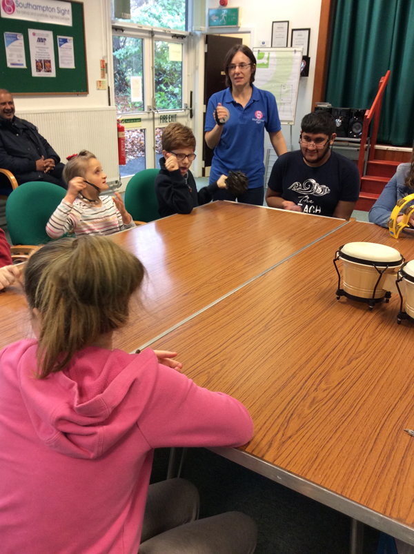 "Here is a picture of some of the group playing the percussion instruments, and singing their song ""My Friend Chic""."