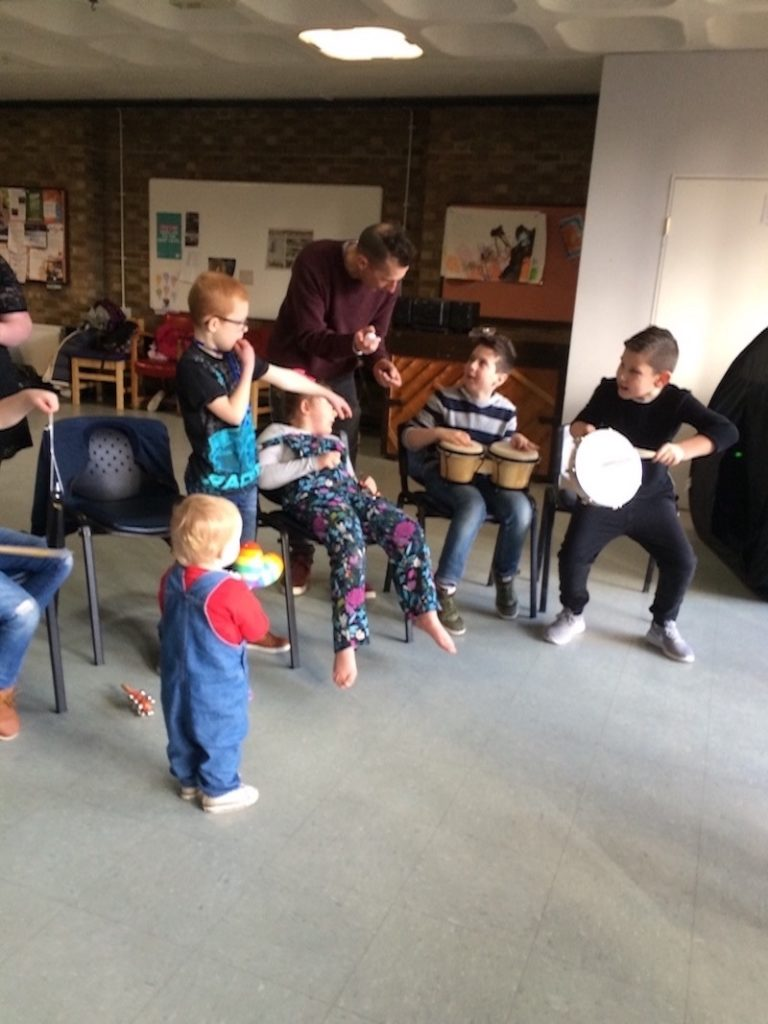 Participants in the group playing percussion instruments, including Bongo Drums, Tunable Hand Drum, Maracas, Shakers, and Cowbell.