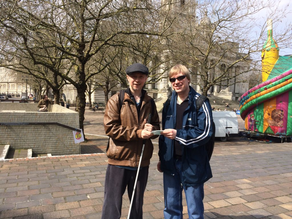 A picture of David from Global Music Visions C.I.C. handing Clarke Reynolds a CD of created backing tracks for his inclusive Art Exhibition.