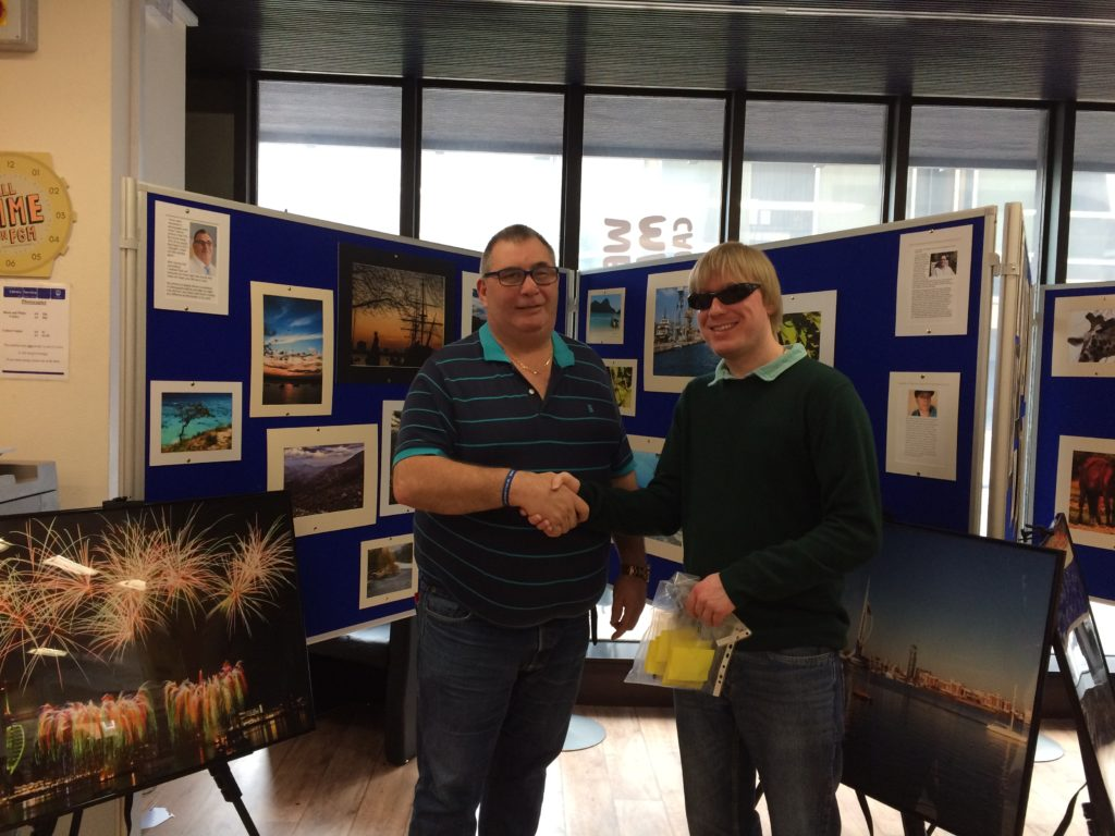 David Shervill handing the Memory Sticks to Dave Taylor in Portsmouth Central Library, Guildhall Square, Portsmouth. They are standing in front of some of the photographs on display.