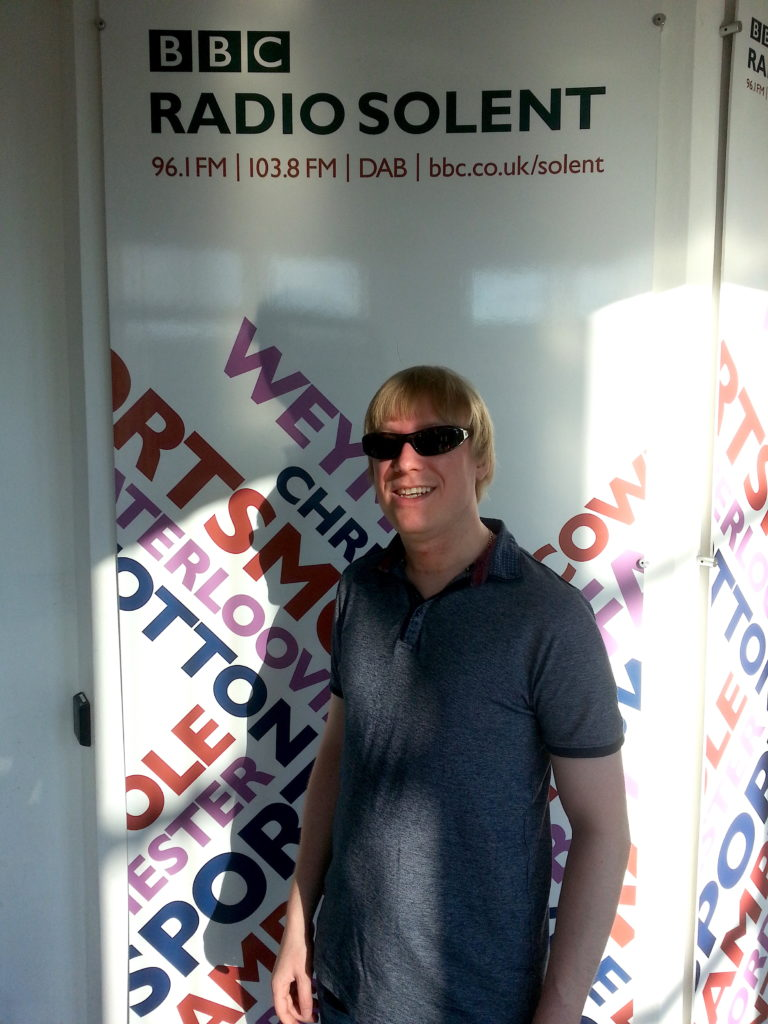 Included is a picture of David, standing in front of the BBC Radio Solent banner.