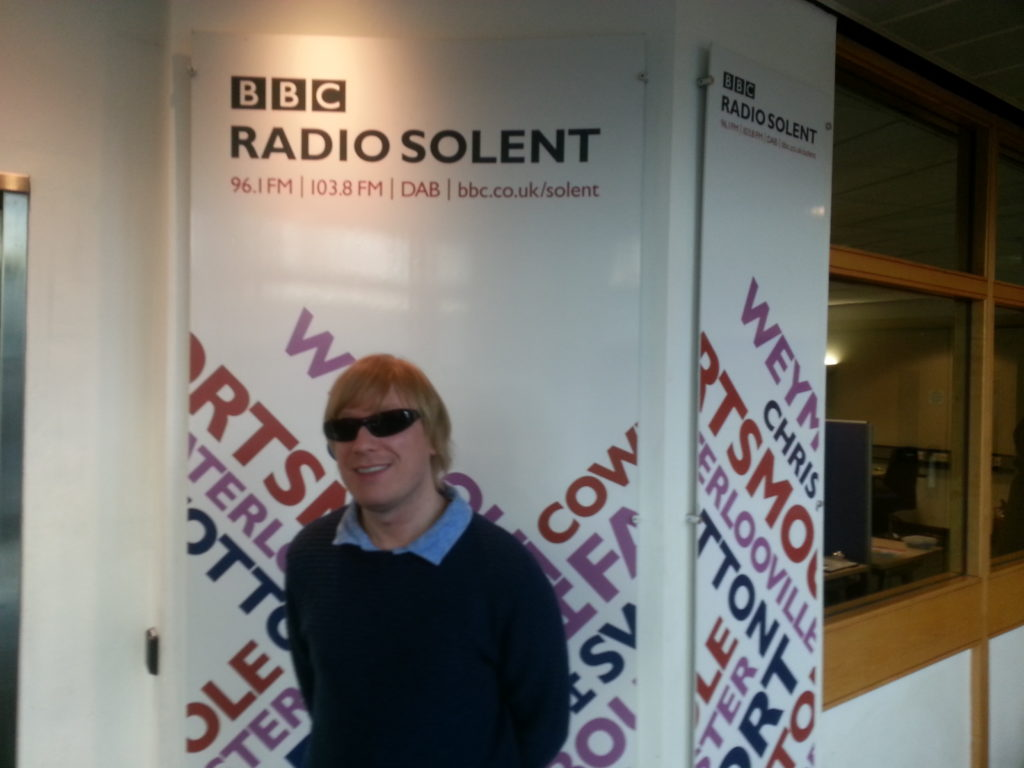 Included is a picture of David standing in front of the BBC Radio Solent banner.