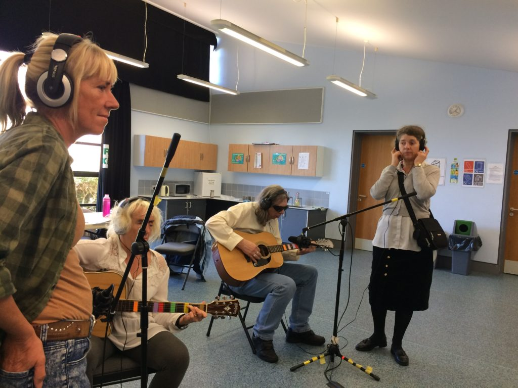 Included is a picture of four participants. Two are sitting behind a microphone playing acoustic guitars, and two others are standing by each microphone, ready to change the position if needed. All the participants are wearing headphones to listen to the recording.