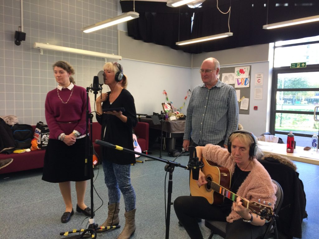 Included is a picture of some of the group recording their song. One participant is singing into the microphone, whilst another is sitting playing the acoustic guitar, which also has a microphone in front of it. Two other participants are standing listening.