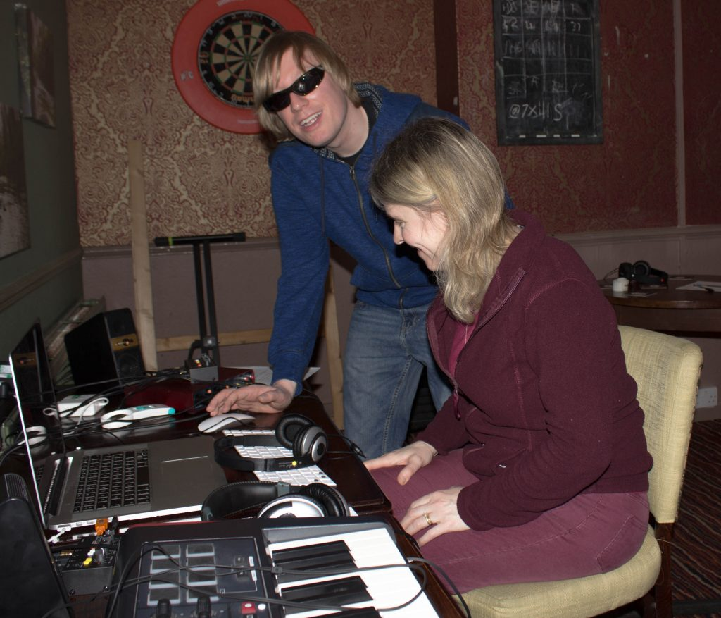 Included is a picture of participant Elena Sommers sitting with the laptop in front of her on a table. There is a MIDI Keyboard on her left and David standing to her right, with headphones on the table in front of them both.