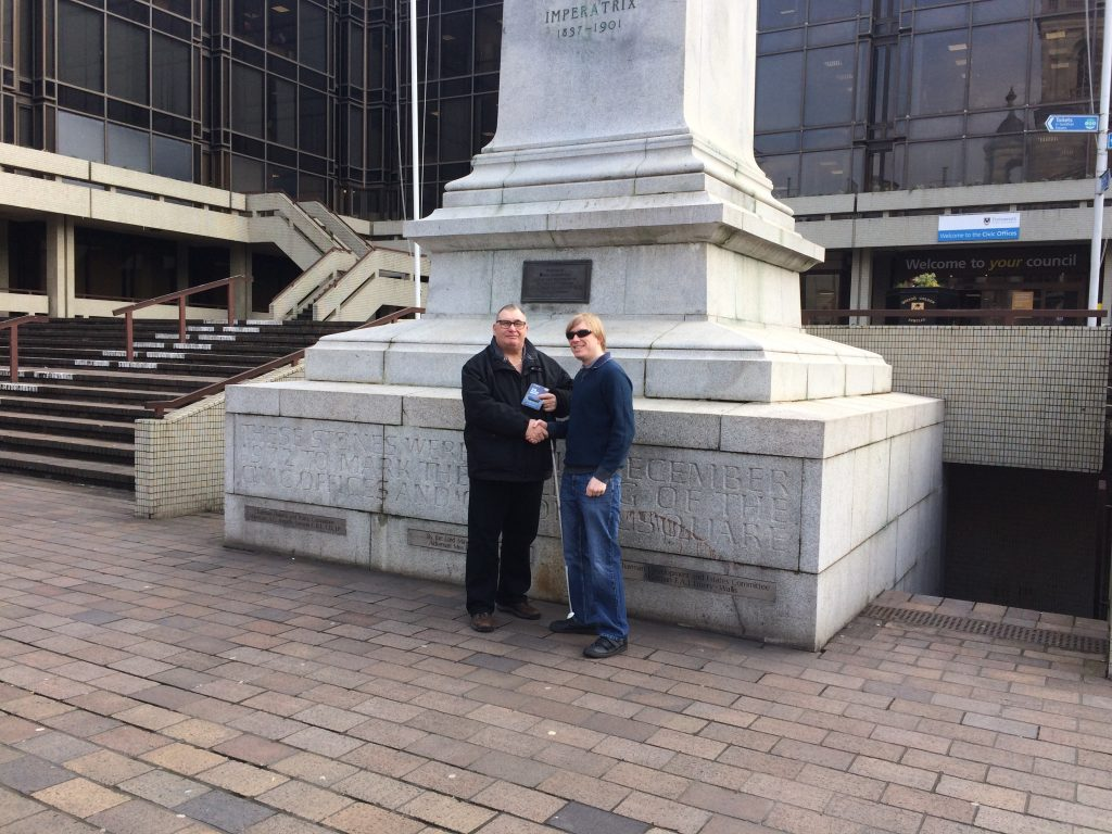 Included is a picture of Dave Taylor from Losing My Sight UK, and David Shervill from Global Music Visions C.I.C. shaking hands, whilst standing in front of the Victoria Monument in Guildhall Square Portsmouth. Dave Taylor is holding the memory stick in his left hand.
