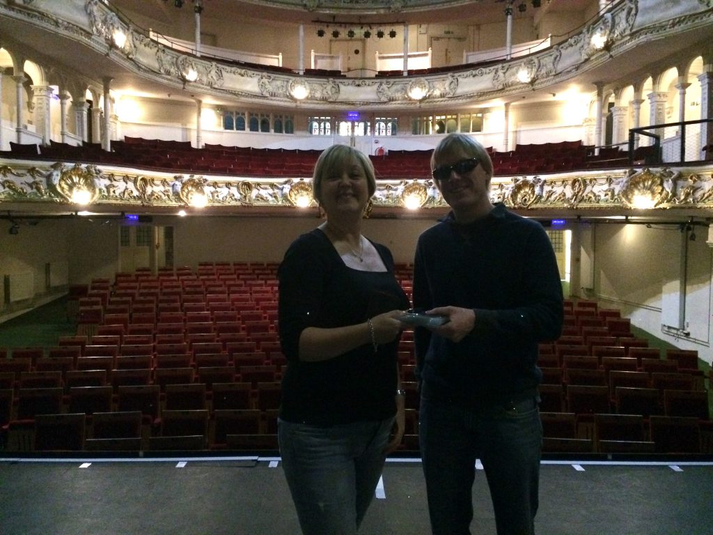 Rachel Goodall from The Red Sauce Theatre Company, and David Shervill from Global Music Visions C.I.C. standing on the stage at the New Theatre Royal, with their backs to the brightly lit auditorium. David is handing the CDs and memory stick to Rachel ready for their rehearsals.