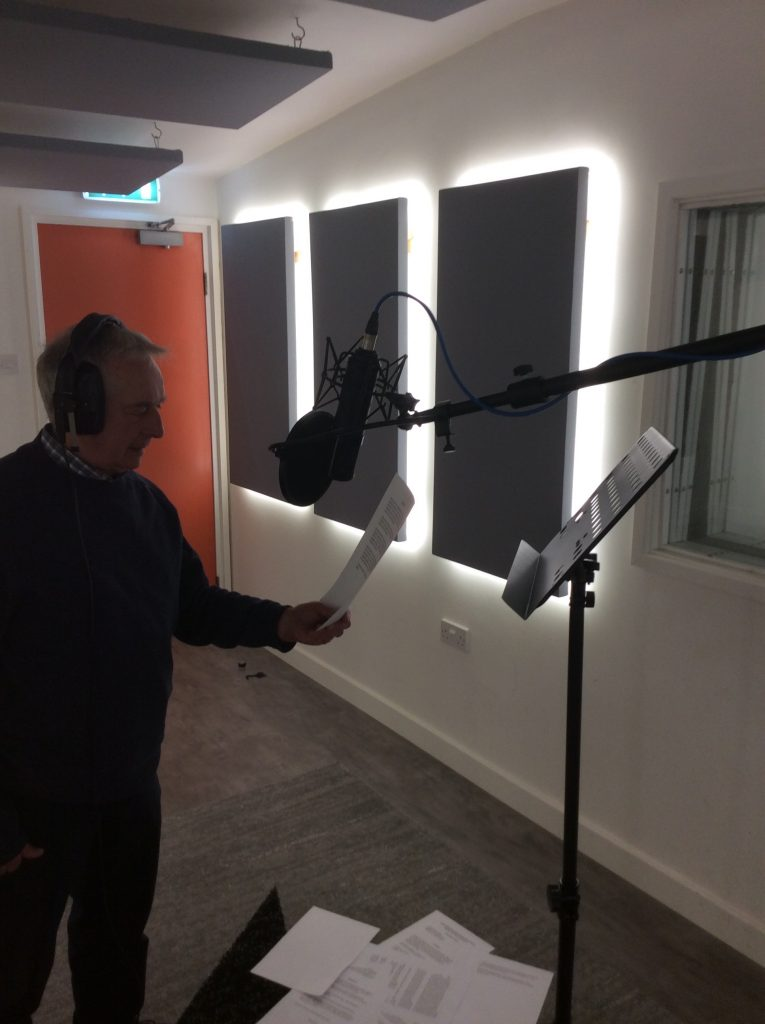 Included is a picture of Richard Miller narrating the audiobook in the studio. He is wearing headphones, and is standing in front of the Microphone holding his script. Old script is on the floor in front of him. There are three rectangular shaped acoustic treatment panels on the right side of the photo, positioned vertically across the wall. There are also panels on the ceiling above him.