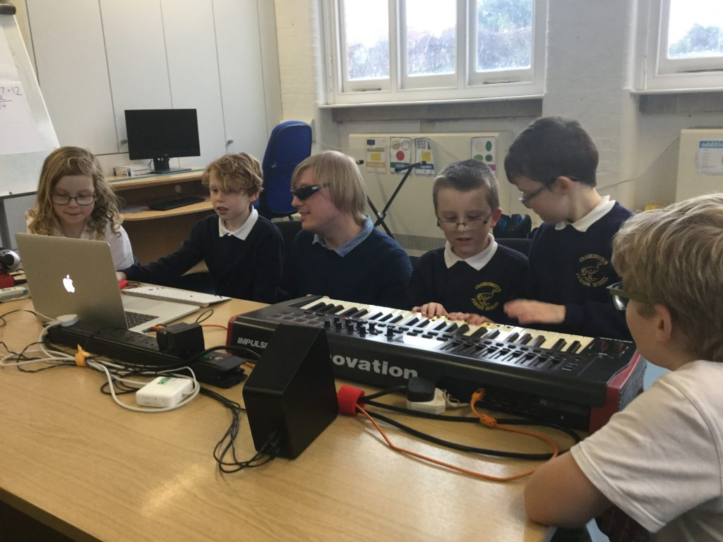 Included is a photo of the group of five pupils. The laptop is open on the table in front of two of the pupils, and the MIDI keyboard is on the table in front of the other three pupils. David is crouching between the two groups of pupils.