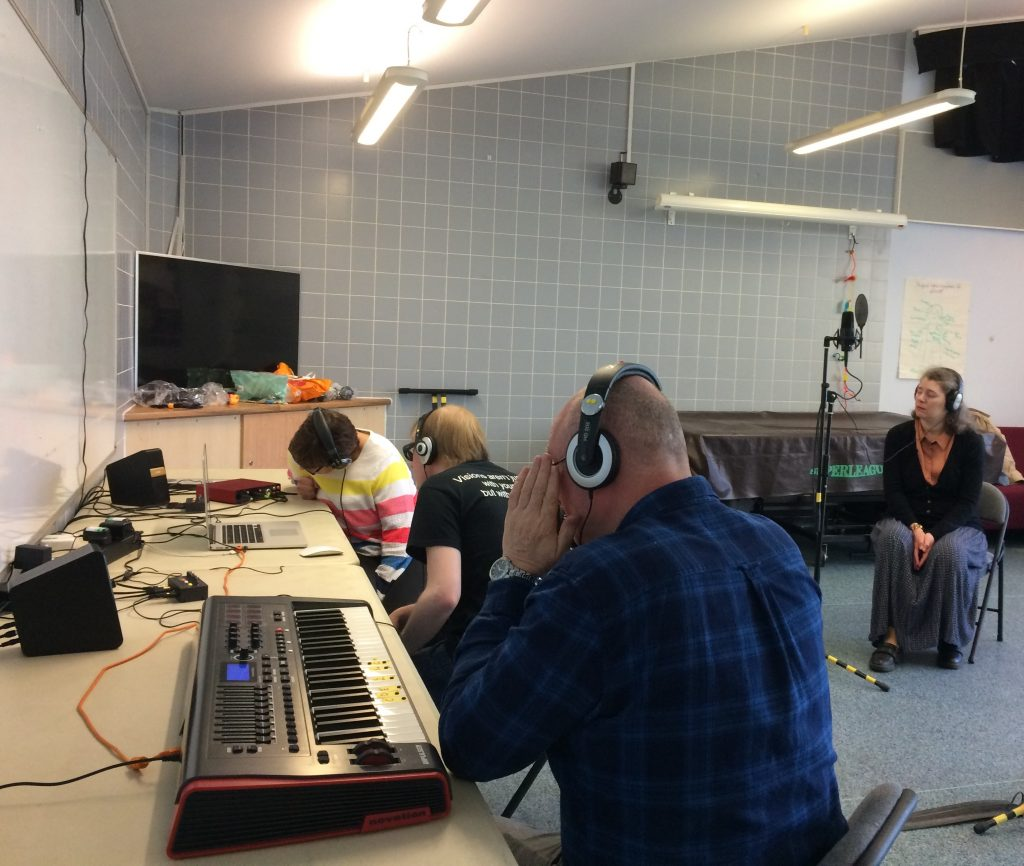Included is a picture of the group. One is sitting on a chair in front of a mic stand, listening to the recording. Another person is sitting at a table in front of the MIDI keyboard, also listening to the recording, whilst a third participant is sitting in front of a laptop monitoring the vocal mic levels, and adjusting when needed, supported by David.