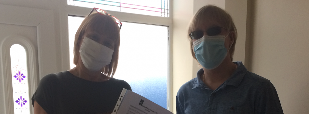 Rachel Goodall and David Shervill standing together, both are wearing face masks, and facing the camera.