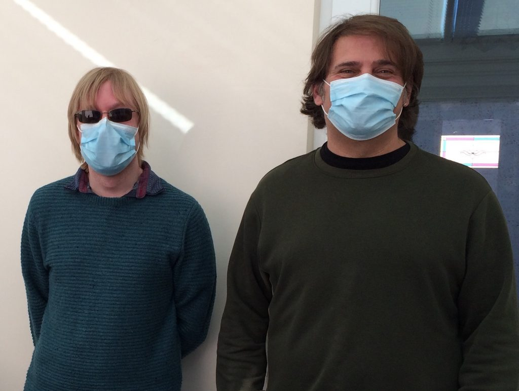 A photo of David and Jim who are facing the camera, wearing face masks.