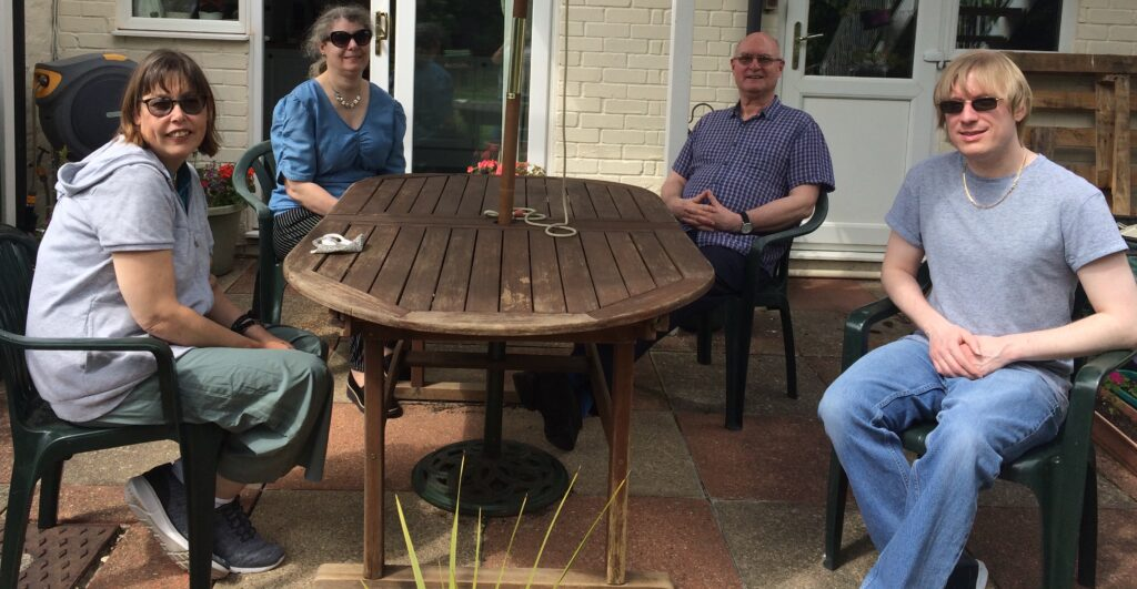 Included is a photo of four people, including David sitting around a garden table outside, all facing the camera.