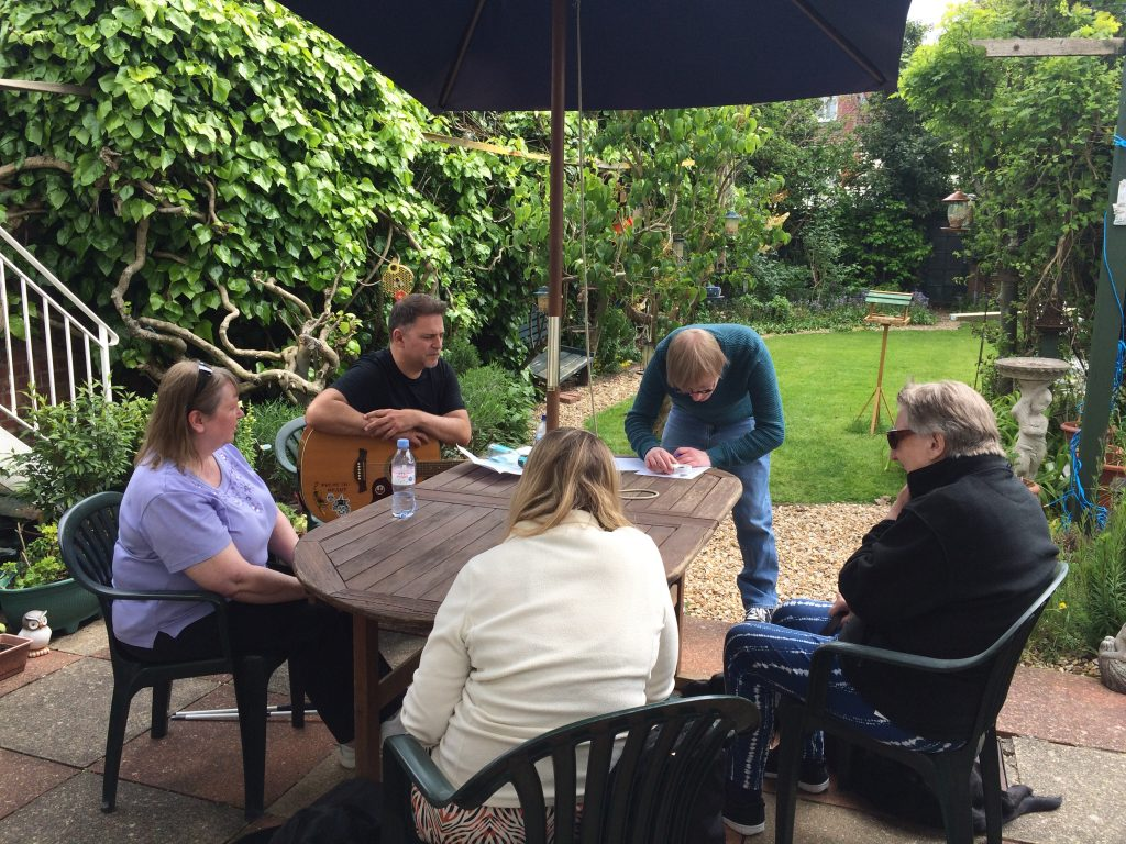 Included is a photo of five people sitting around a garden table outside, with trees and hedgerows around them. They are working through their lyrics, and one person is holding an acoustic guitar.