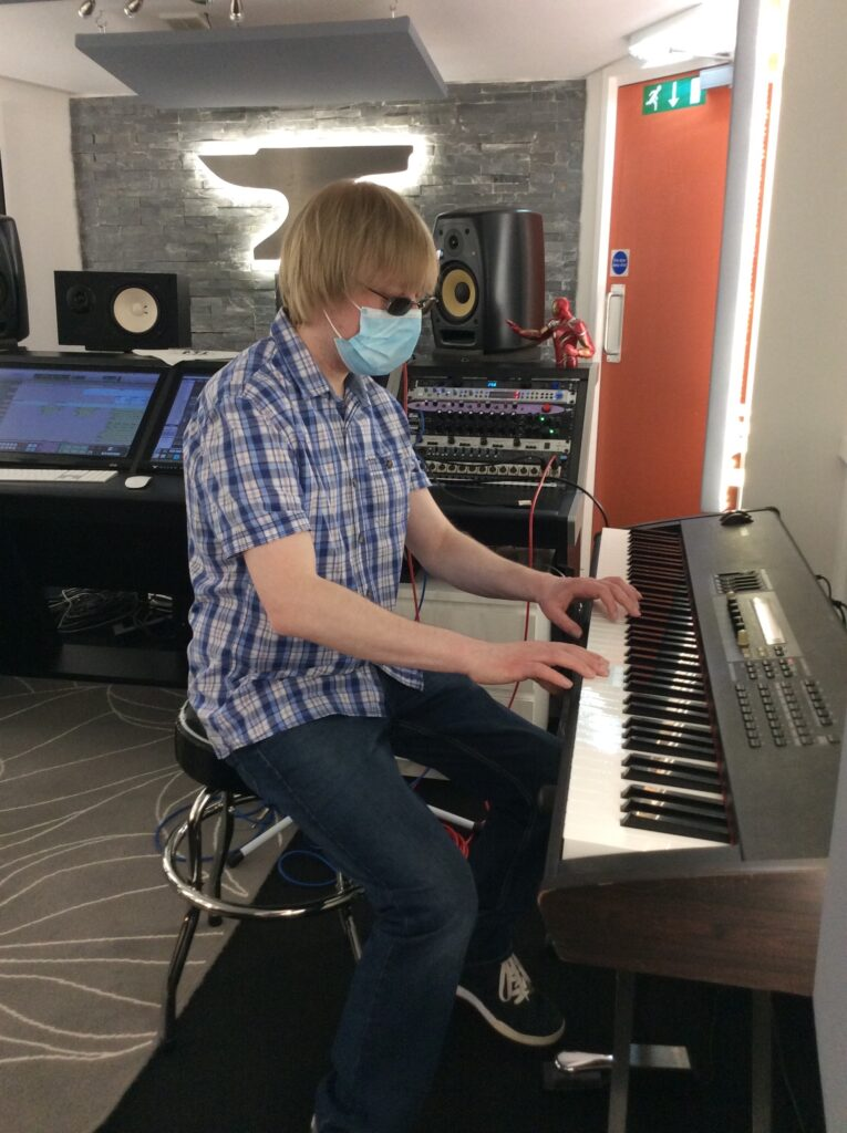 Included is a side view photo of David playing a keyboard. There are computer screens, effects units, and speakers in the background. The shape of an Anvil is visible on the back wall.